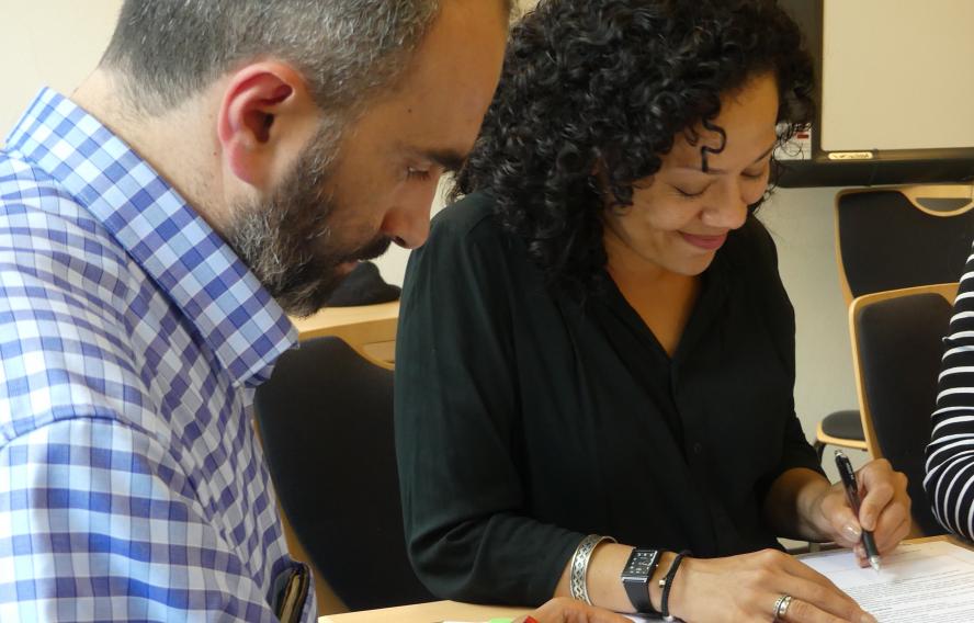 Ein Mann und eine Frau sitzen nebeneinander an einem Tisch. Sie lernen und schreiben etwas auf ein Blattpapier. Die FRau lächelt.