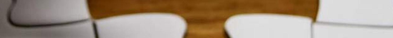 Zwei Puzzelteile liegen nebeneinander auf einem Holztisch. Sie sind noch nicht ineinander gefügt.
